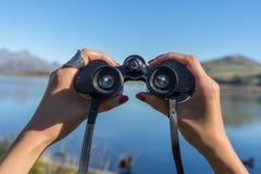 Hands holding binoculars Stock Photo