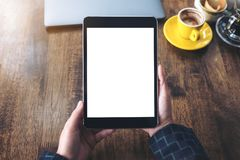 Hands holding black tablet pc with blank white desktop screen with laptop and coffee cups on wooden table in cafe. Top view mockup image of hands holding black Royalty Free Stock Photo