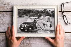 Hands holding black-and-white photo of seniors in picture frame Stock Photo