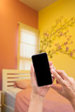 Hands holding blank black screen smartphone in bed room. Stock Image