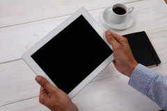 Hands holding blank digital tablet, notepad and cup of coffee  Stock Image