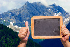 Hands holding a blank slate blackboard in the air Stock Photography