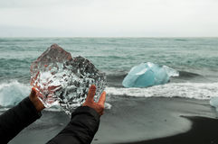 Hands holding a block of pristine glacier ice. In Iceland with sea in the background Stock Photography