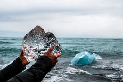 Hands holding a block of pristine glacier ice. In Iceland with sea in the background Royalty Free Stock Photos