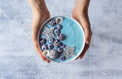 Hands Holding Blue Yogurt Berry Smoothie Bowl. An anonymous woman`s hands holding a blue smoothie bowl topped with frozen berries and dragon fruit. The smoothie Royalty Free Stock Photo