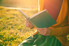 Hands holding book and reading. In summer sunset light Royalty Free Stock Image