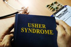 Hands holding book Usher syndrome. Hands holding book Usher syndrome and diagonsis form Royalty Free Stock Photo