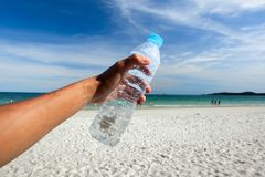Hands holding bottle in front of beautiful azure sea.  Stock Images