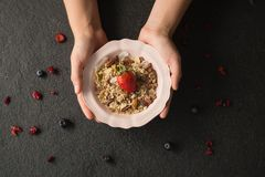 Hands holding a bowl of fruit cereal. Close-up of hands holding a bowl of fruit cereal Stock Photos