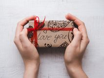 Hands holding a box with a gift, tied by a ribbon royalty free stock photo