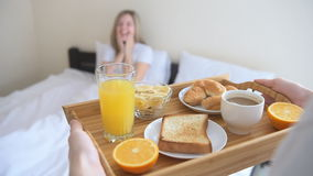 Hands holding breakfast tray for happy woman. stock video
