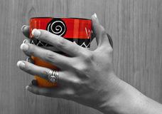 Hands holding a bright red cup Stock Photography