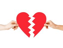 Hands holding broken heart. Love and relationship problems concept - male and female hands holding two parts of broken heart Royalty Free Stock Images