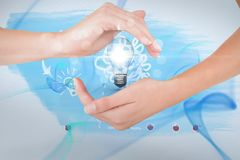Hands holding bulb against blue background Royalty Free Stock Photo