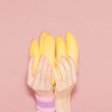 Hands holding bunch of bananas. Fashion, vanilla style minimalis Stock Photos
