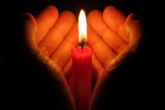 Hands holding a burning candle. In dark Royalty Free Stock Photo
