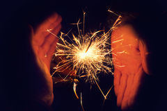 Hands holding a burning sparkler. Bright festive Christmas sparkler. Beautiful bright celebratory sparkler surrounded by female and male hands. Sparkler. Couple Royalty Free Stock Photo
