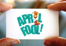 Happy April Fools Day design. Hands holding busines scard with April Fools message. Hands holding business card with April Fools message. Macro photo of fingers Royalty Free Stock Image