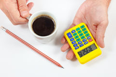 Hands holding a calculator and cup of coffee on white background Royalty Free Stock Photos