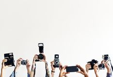 Hands are holding cameras with white background royalty free stock photography