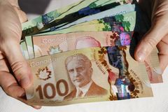 Hands holding Canadian Cash Stock Photo