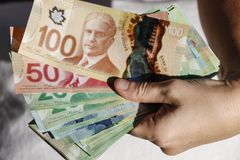 Hands holding Canadian Cash. Hands holding a pile of Canadian Cash royalty free stock photos