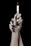 Hands holding a candle, a candle is lit, black background, solitude, warmth, in the dark, Hands death, hands witch Stock Photos