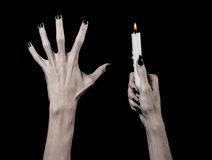Hands holding a candle, a candle is lit, black background, solitude, warmth, in the dark, Hands death, hands witch. Studio royalty free stock image