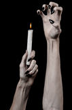 Hands holding a candle, a candle is lit, black background, solitude, warmth, in the dark, Hands death, hands witch. Studio stock image