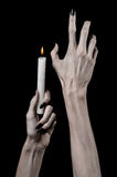Hands holding a candle, a candle is lit, black background, solitude, warmth, in the dark, Hands death, hands witch. Studio stock photography