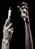 Hands holding a candle, a candle is lit, black background, solitude, warmth, in the dark, Hands death, hands witch. Studio royalty free stock images