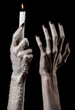 Hands holding a candle, a candle is lit, black background, solitude, warmth, in the dark, Hands death, hands witch. Studio stock photos