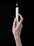 Hands holding a candle, a candle is lit, black background, solitude, warmth, in the dark, Hands death, hands witch Stock Photo