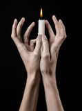 Hands holding a candle, a candle is lit, black background, solitude, warmth, in the dark, Hands death, hands witch. Studio royalty free stock photo