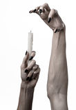 Hands holding a candle, a candle is lit, white background, solitude, warmth, in the dark, Hands death, hands witch. Studio stock image