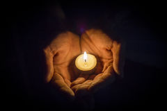 Hands holding a candle. In the dark Stock Images