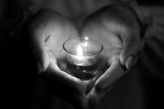 Hands holding candle. In the dark. shallow depth of field Royalty Free Stock Image