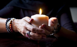 Hands holding a candle. Female hands holding a burning candle Royalty Free Stock Photo