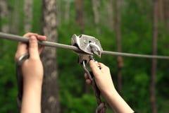 Hands holding carabiner on zip line. Zip line activity. Hands holding carabiner on zip line in forest royalty free stock photos