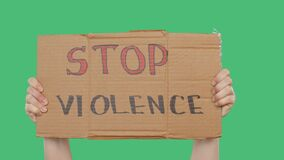 Hands holding cardboard with stop violence sign on green chromakey background. Hands showing inscription stop violence