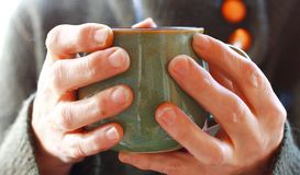 Cup of Morning Tea. Hands holding a ceramic cup of fresh tea in the morning royalty free stock images