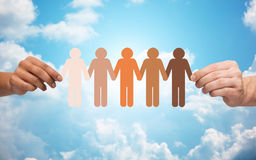 Hands holding chain of people pictogram over sky Stock Images