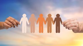 Hands holding chain of people pictogram over sky. Population, race and ethnicity concept - multiracial couple hands holding chain of people pictogram over Stock Photos
