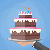 Hands holding chocolate layer cake. Cartoon hands holding chocolate layer cake decorated with three candles. vector illustration in flat design on blue Stock Photos