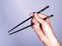 Hands holding chopsticks. Close up of person' hands holding pair of chopsticks, light mauve background Royalty Free Stock Photo