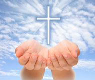 Hands holding Christian cross with light beams. Over sky Stock Photography