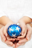 Hands holding christmas bauble Stock Image