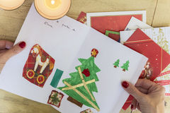Hands holding Christmas Card. Woman hands with red fingernails holding beautiful Christmas card made by a child on wooden table where more cards are placed to be Royalty Free Stock Images