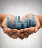 Hands holding city over gray concrete background Royalty Free Stock Photos