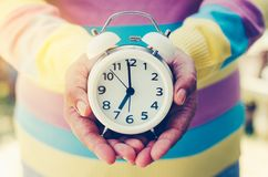 Hands holding a clock give the concept a time. Royalty Free Stock Photography